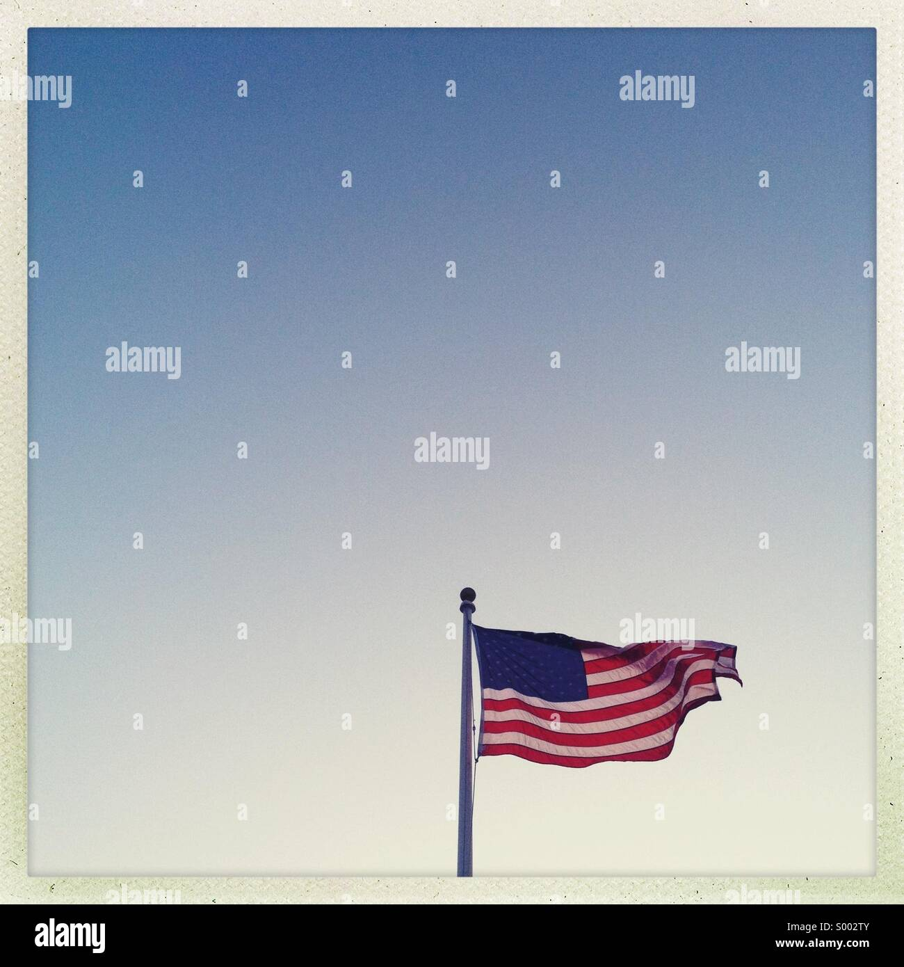 An American flag with clear empty sky - Stock Image