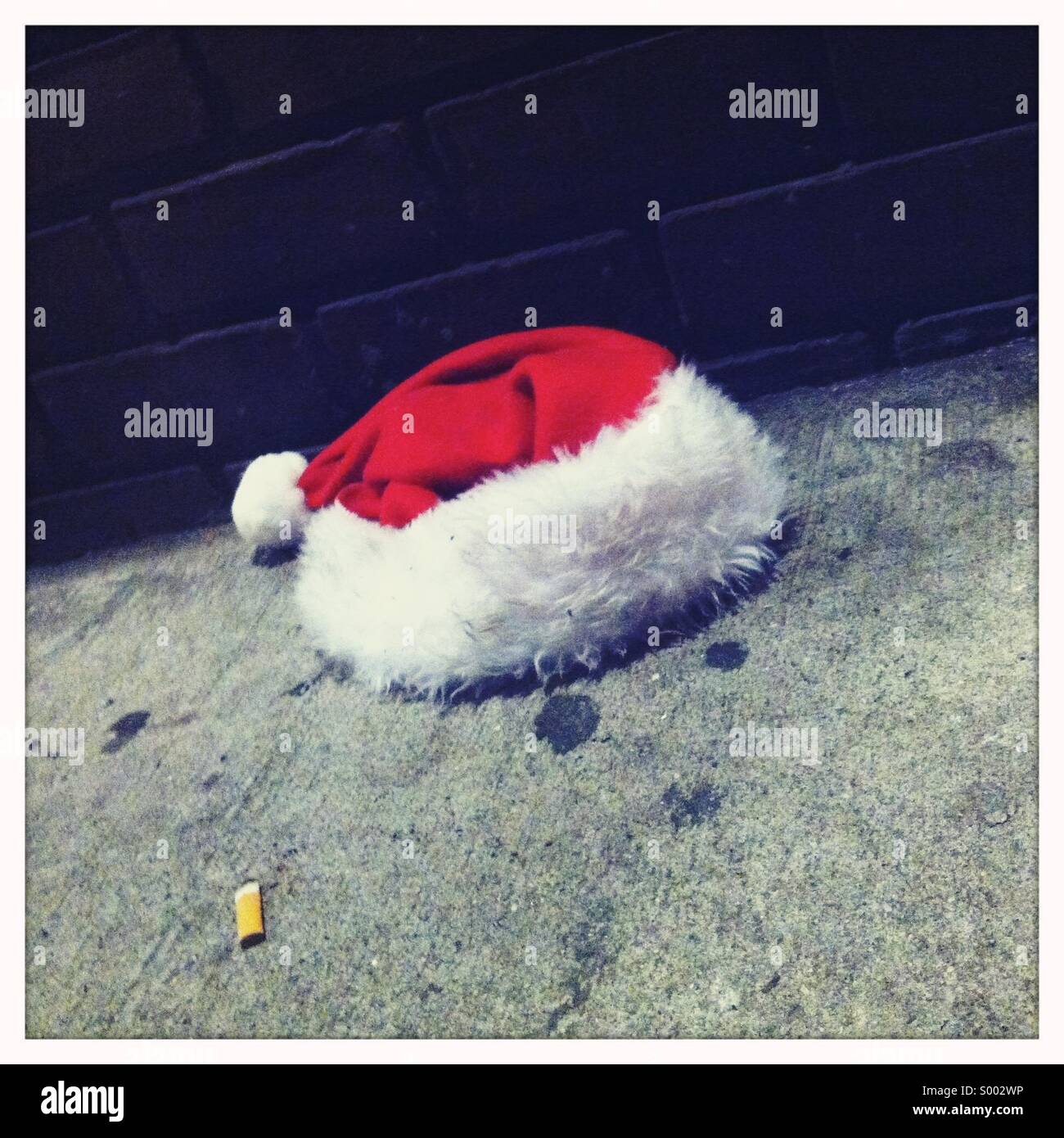 A red and white Santa's hat on a dirty sidewalk - Stock Image