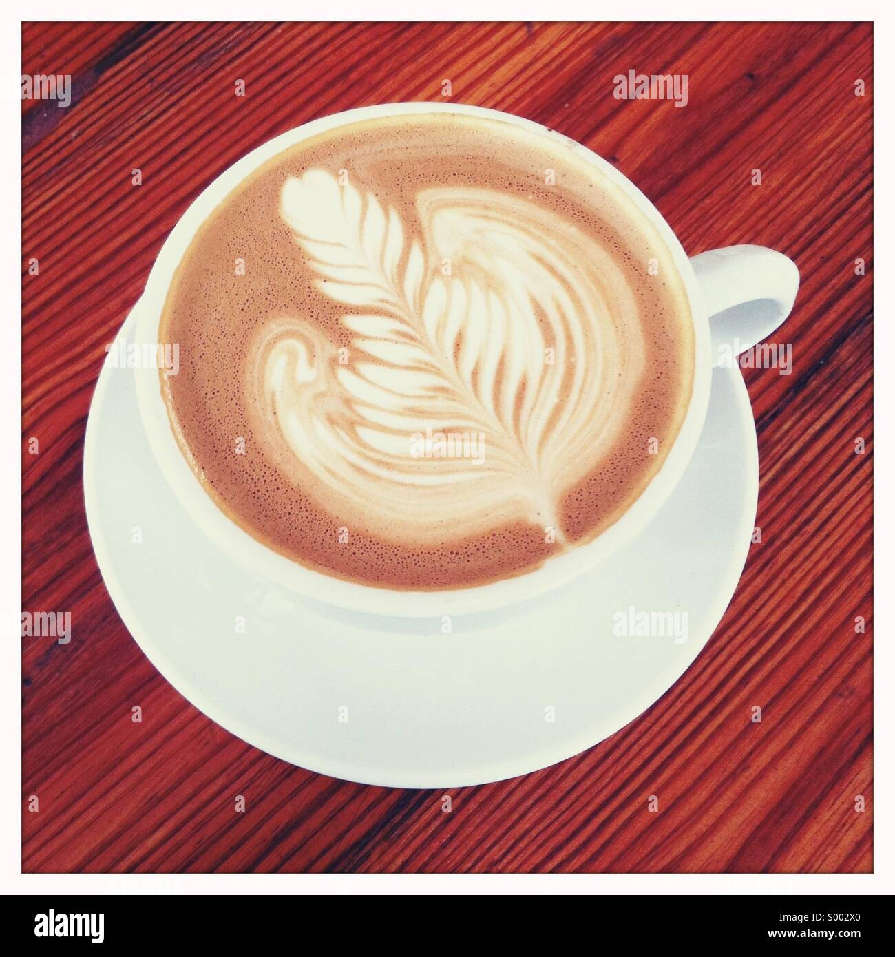 Looking down on a coffee drink in cup with a decorated garnish - Stock Image