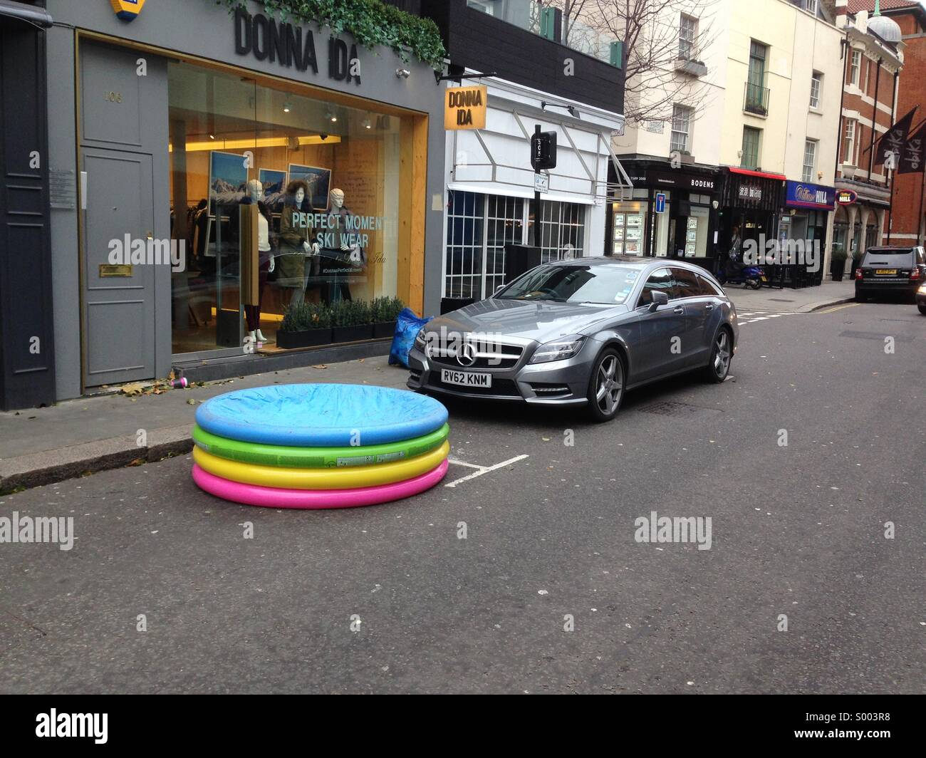 An inflatable swimming pool in used to secure a parking space in Central London - Stock Image