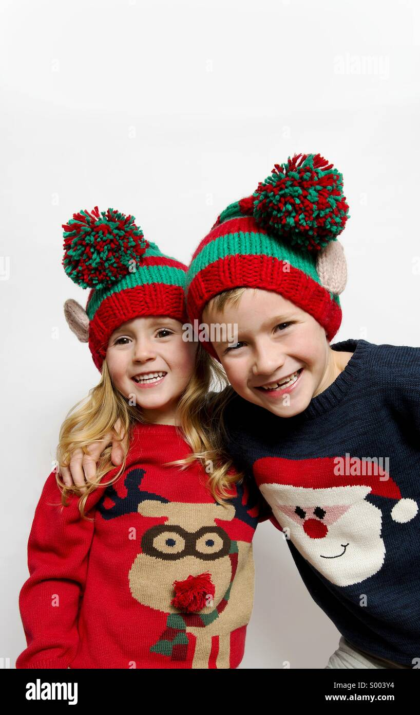 9184ec94dbac1 Young boy and girl posing in Christmas jumpers and wooly elf hats smiling  happy brother and