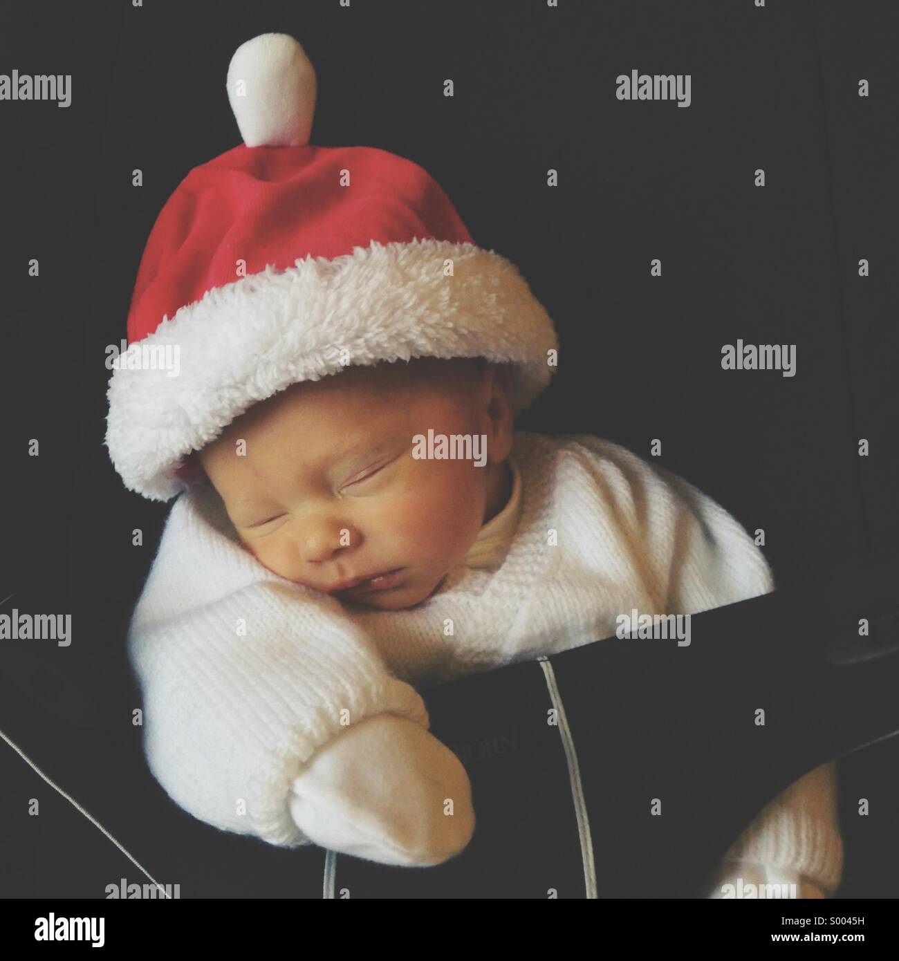 Newborn baby in a Santa hat asleep in a chair. - Stock Image