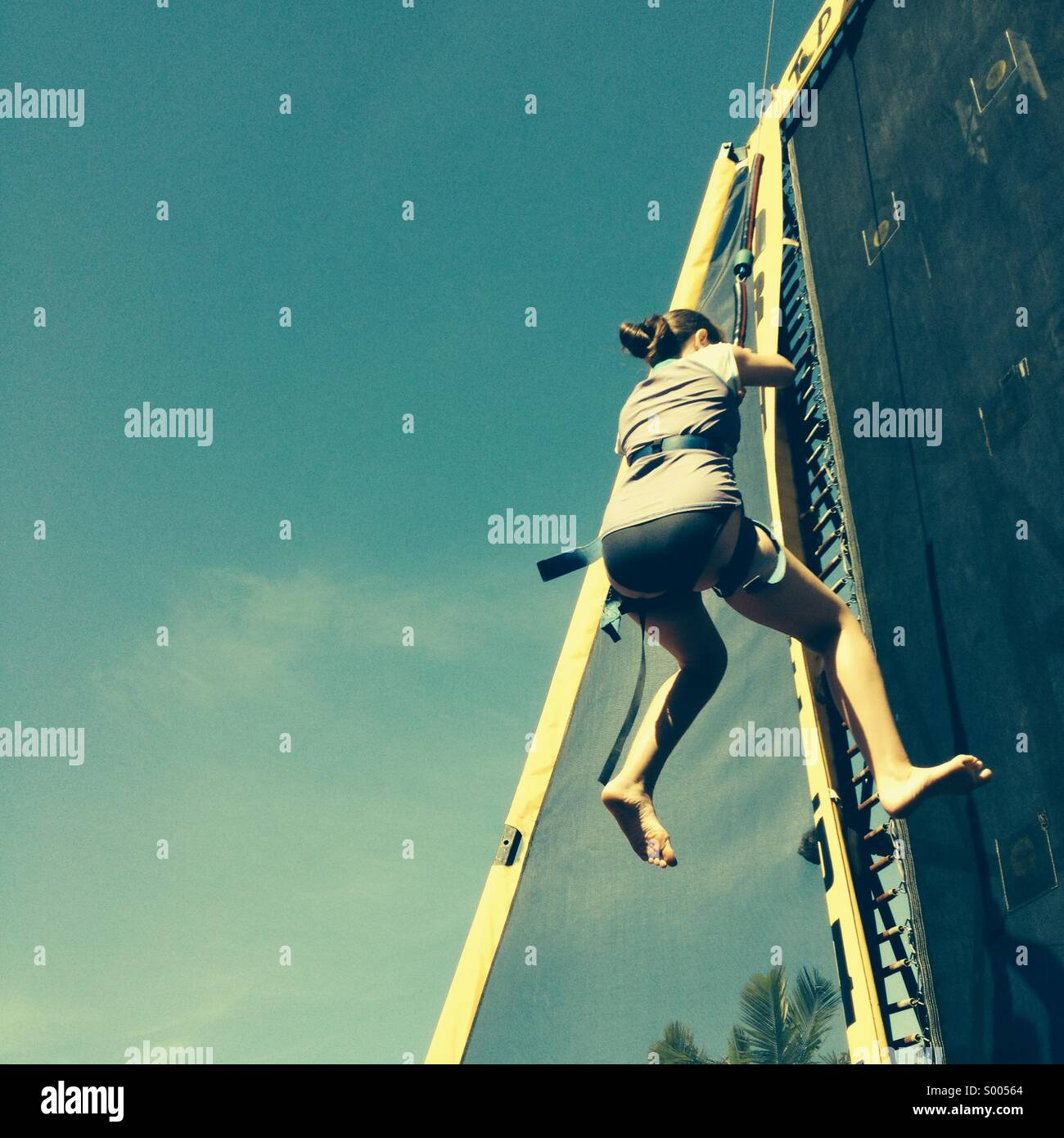 Girl climbing on an abseiling wall. Stock Photo