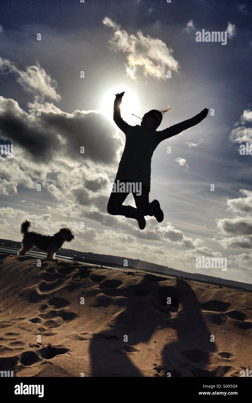 A woman jumps for joy on a sunny day at the beach in Devon, UK. Beautiful blue skies and white fluffy clouds are - Stock Image