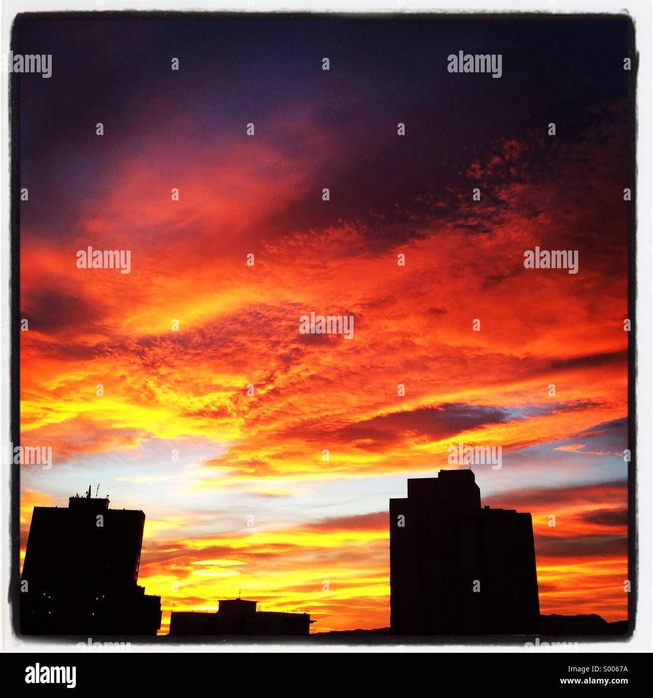 Dramatic sky at sunset with silhouetted buildings - Stock Image
