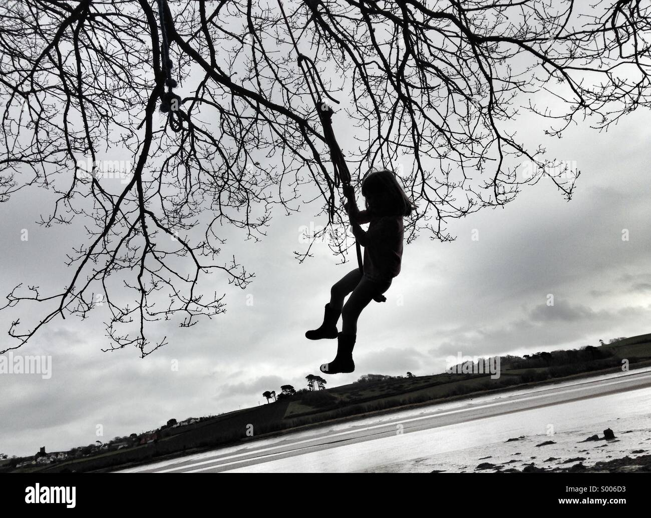 Girl child swings on rope from a tree. Adventures on the river bank. - Stock Image