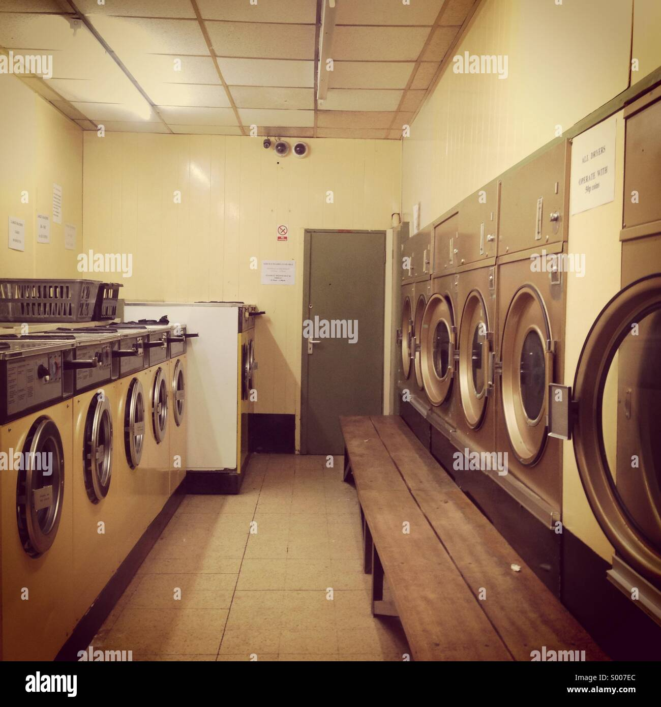 Laundrette shop with washing machines and dryers. - Stock Image