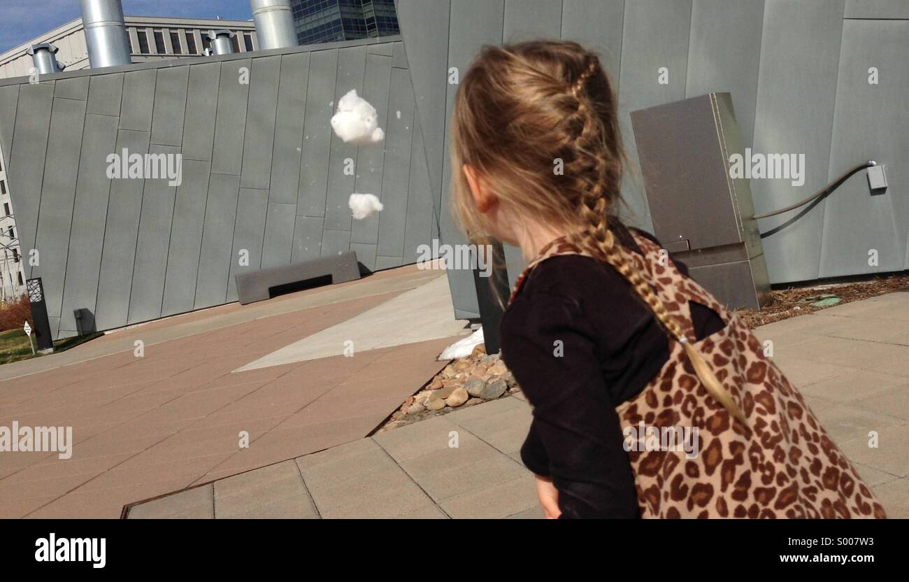 Little girl throws snowball. Stock Photo