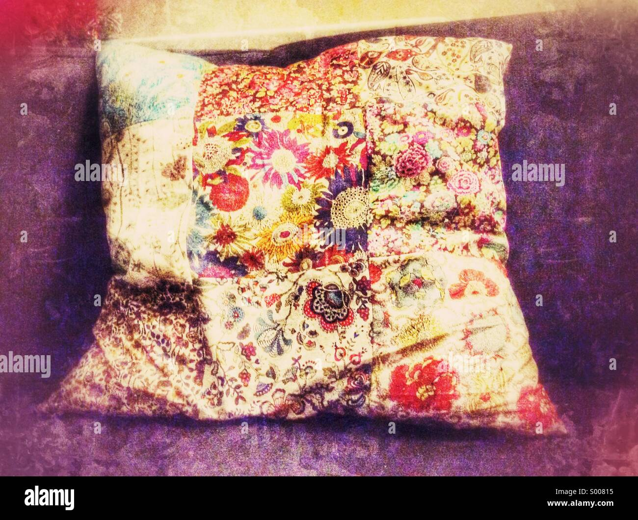 Bright floral patchwork cushion on a comfy sofa - Stock Image