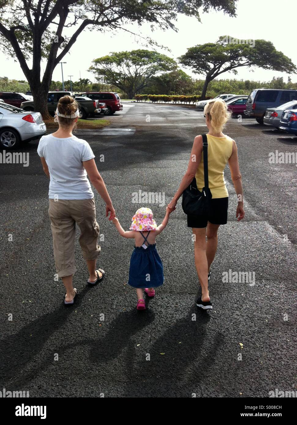 Two women & little girl hold hands in tropical parking lot. - Stock Image