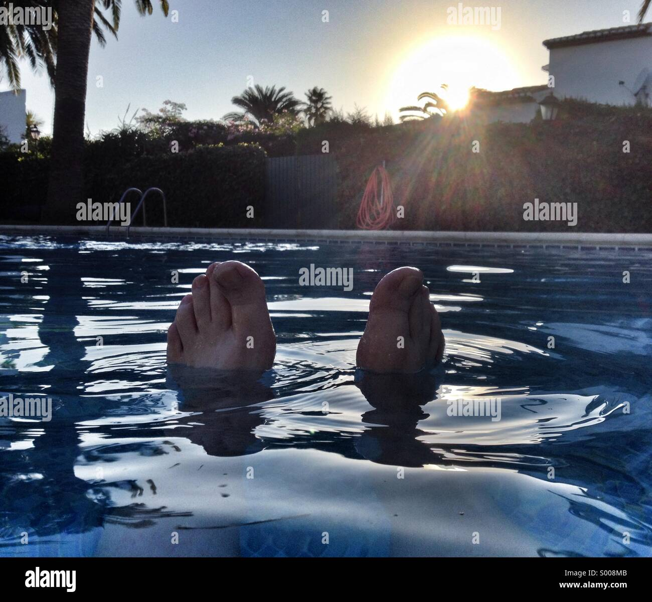 Feet sticking out from a swimming pool at a Spanish villa. - Stock Image