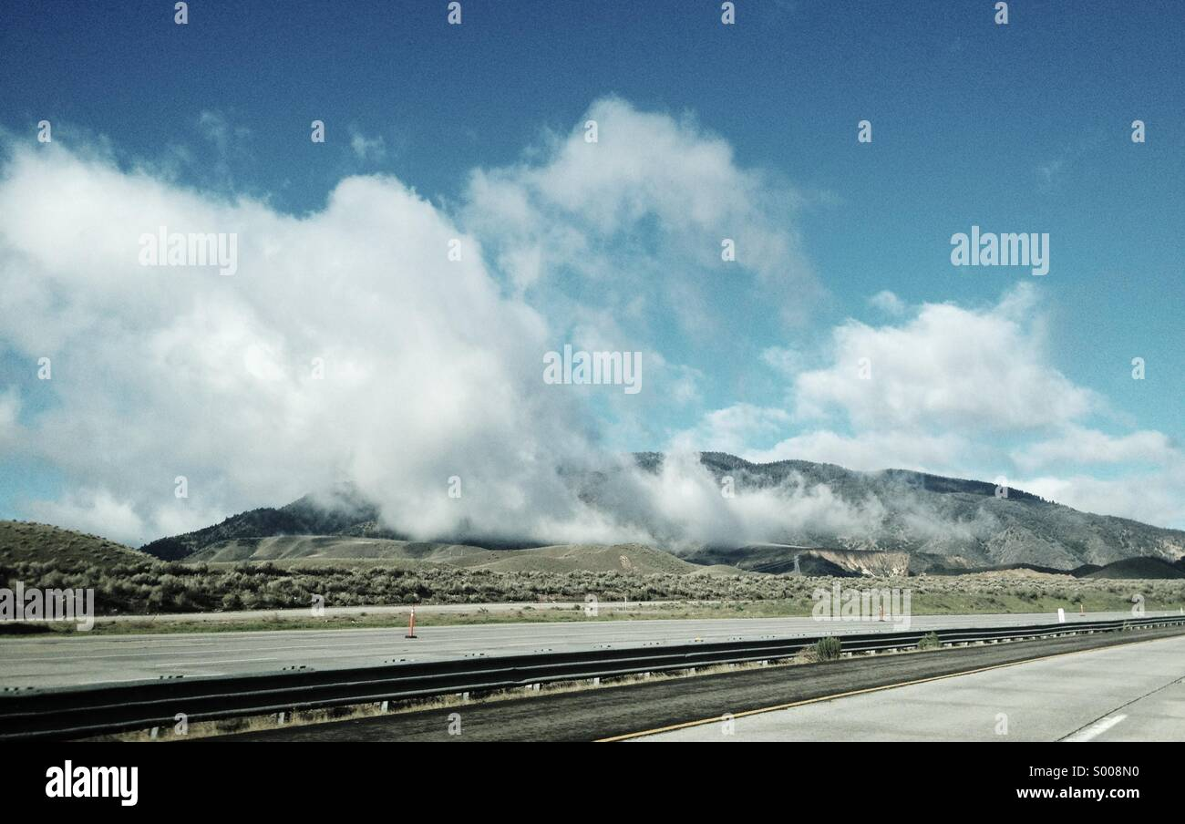 High up in the hills, a storm has passed and clouds drift over the open road. Stock Photo