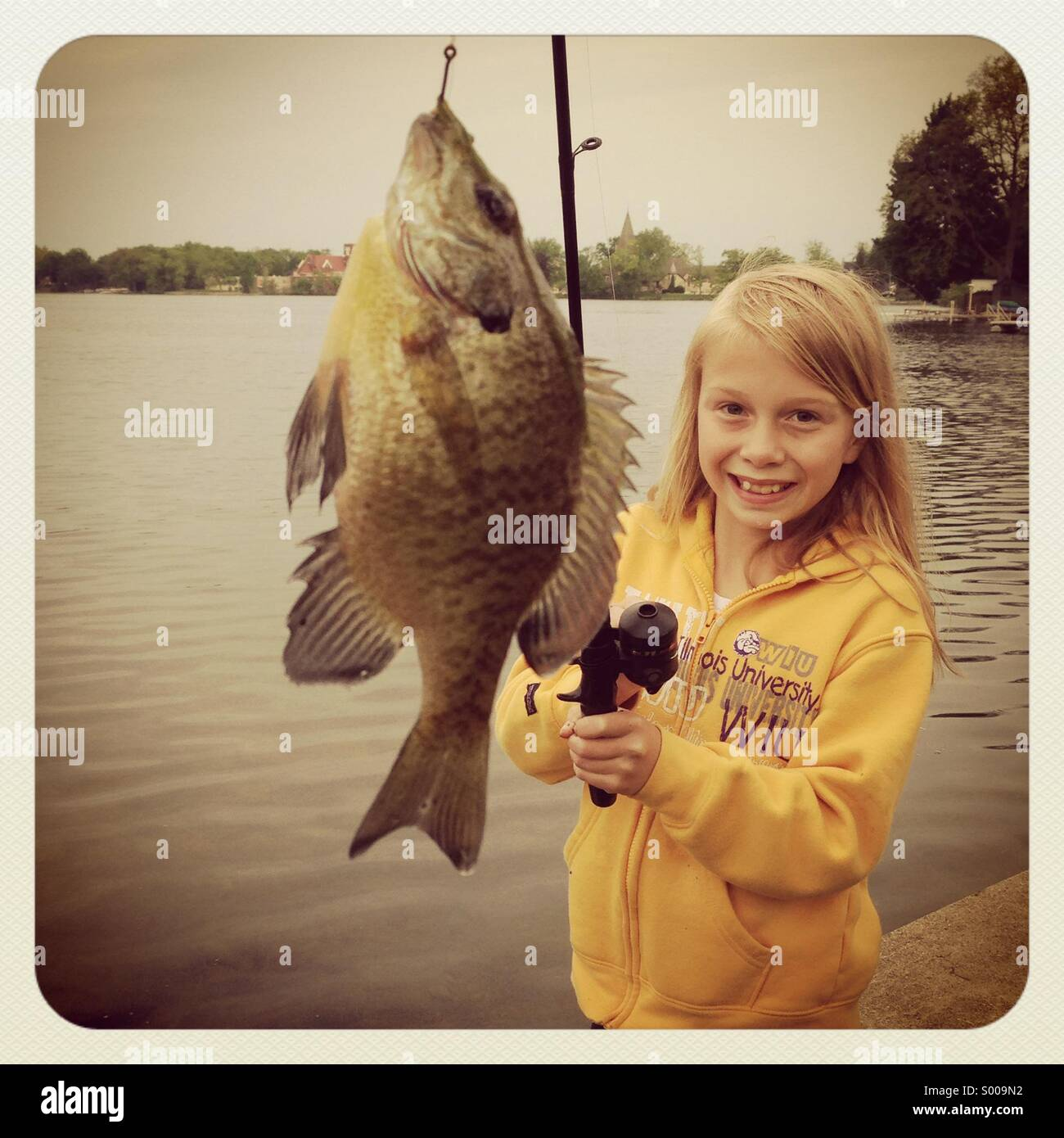 A little girl reels in a little fish. - Stock Image
