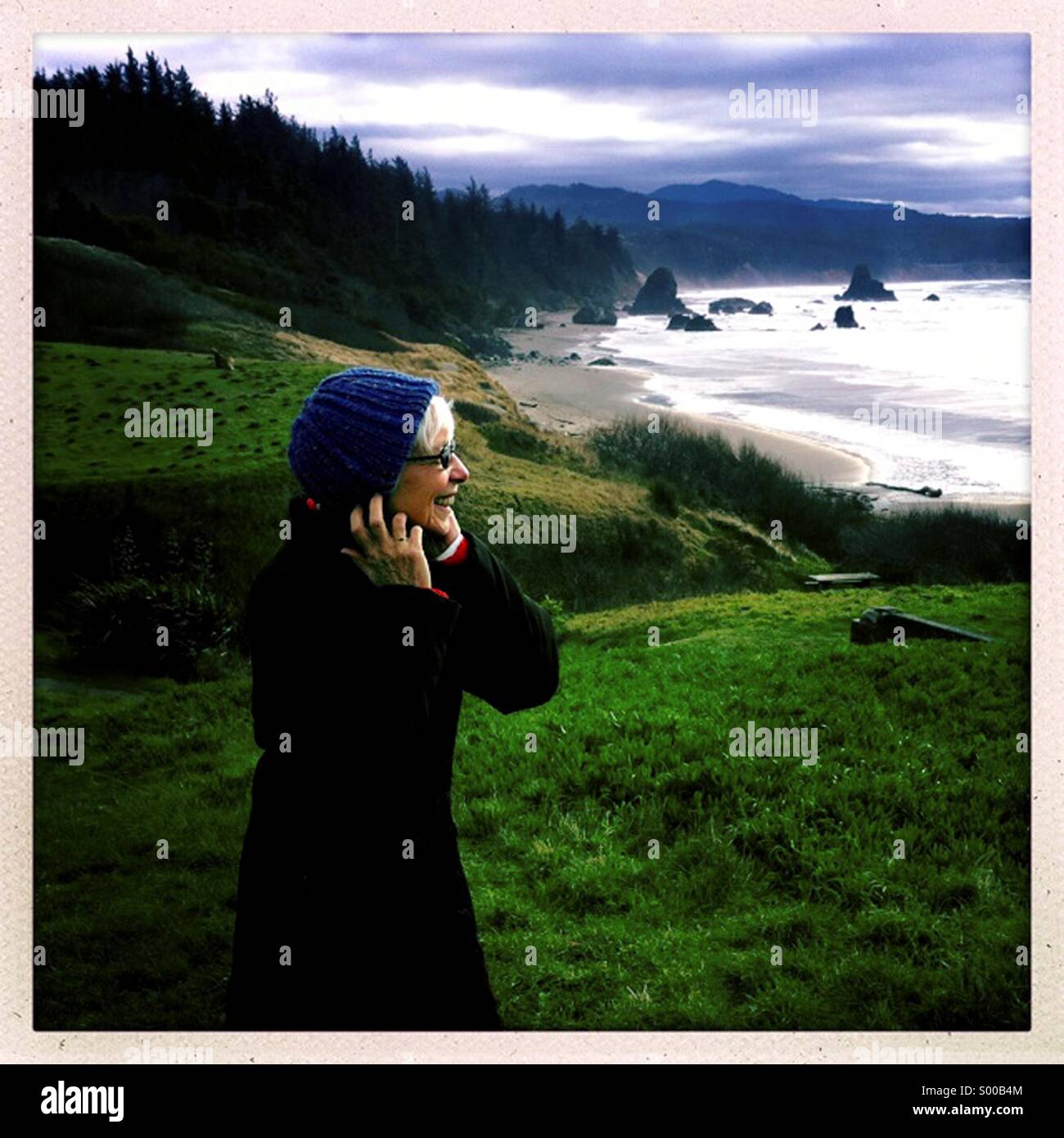 Woman playing with the wind on the Pacific Ocean coastline in nortern Oregon. - Stock Image