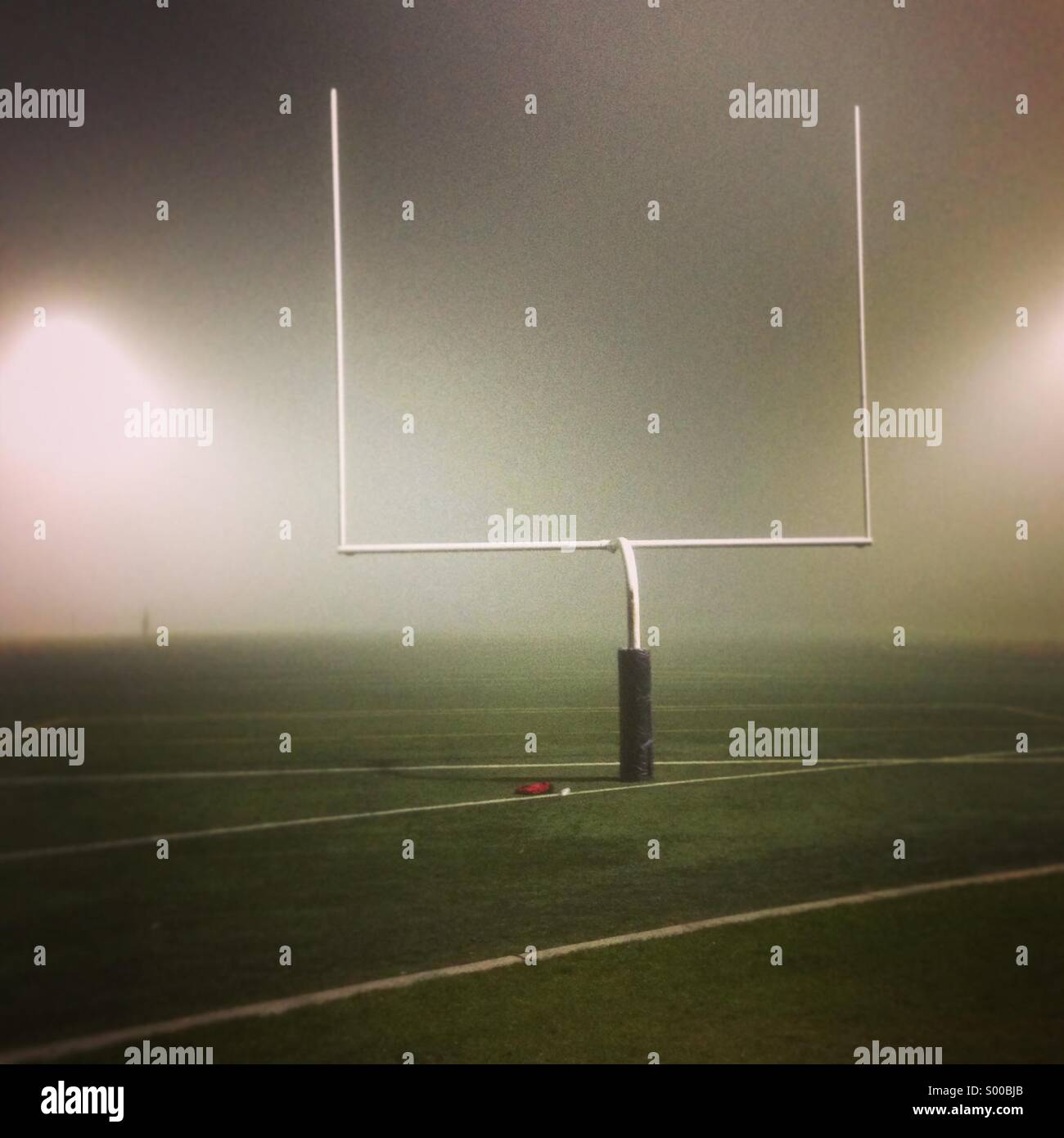 Football field and goal post enveloped in fog at night - Stock Image