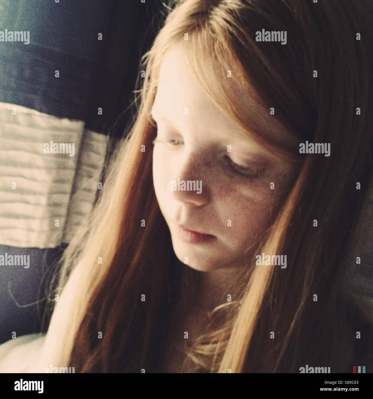 A Young Girl Looks Down While Sunlight Lights Up One Side