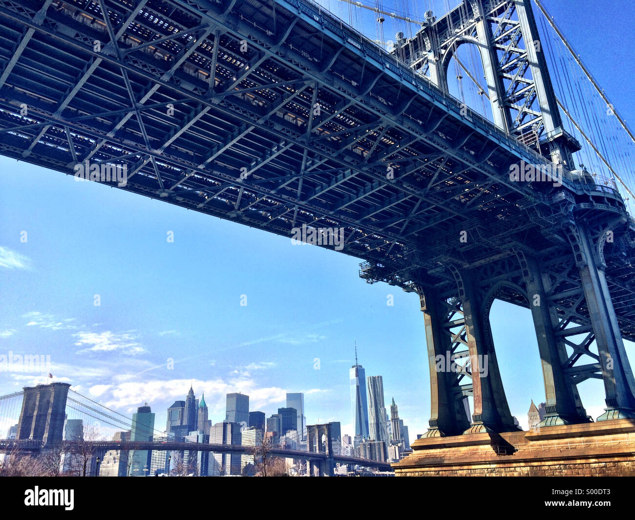 View of the Manhattan and Brooklyn Bridges with Lower Manhattan skyline as seen from the DUMBO neighborhood in Brooklyn, - Stock Image