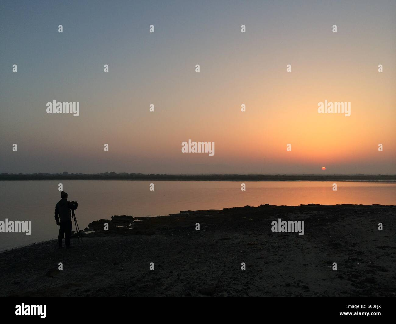 'Early Bird' A photographer capturing the morning sun - Stock Image