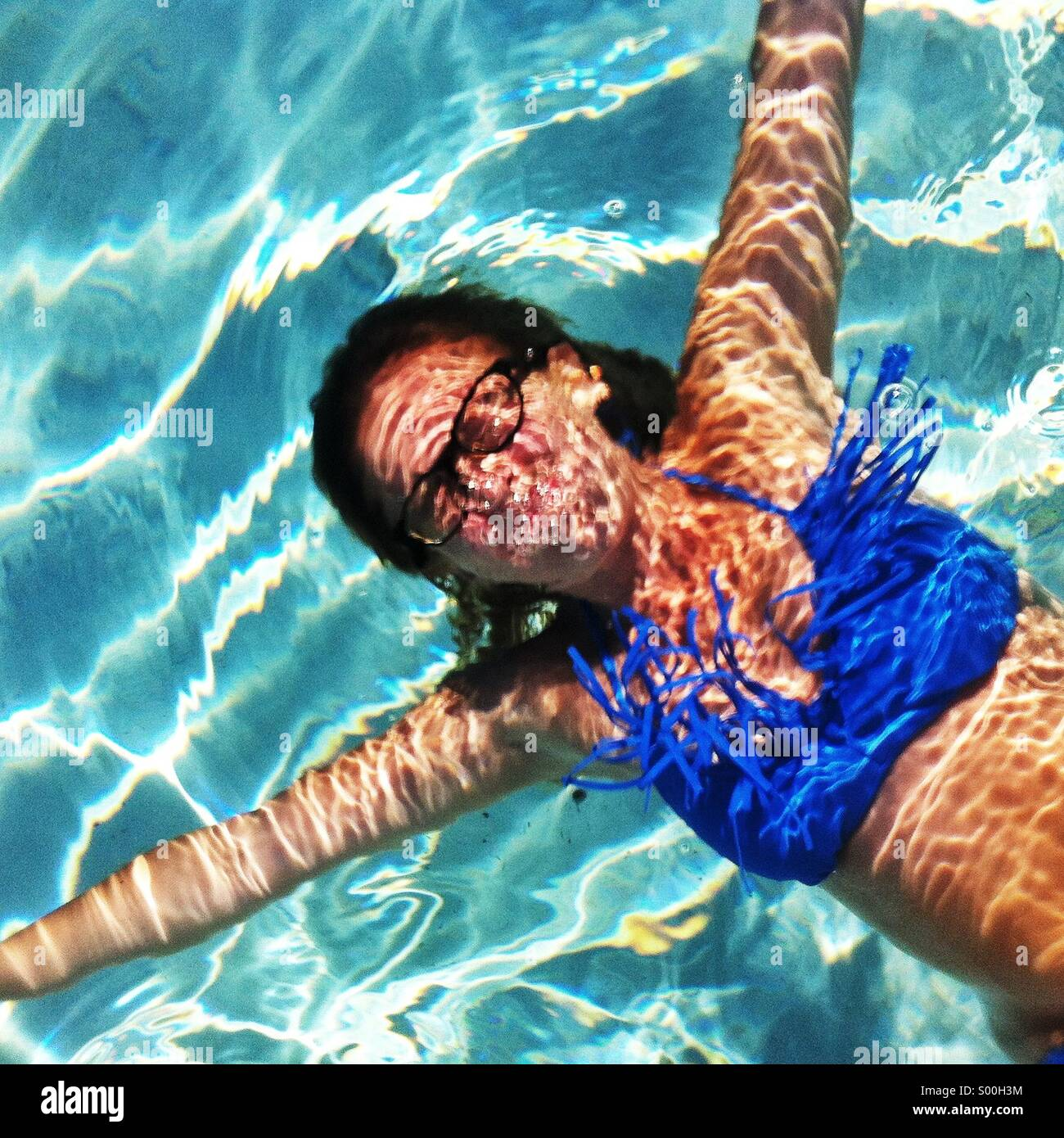 Woman with glasses underwater in pool - Stock Image