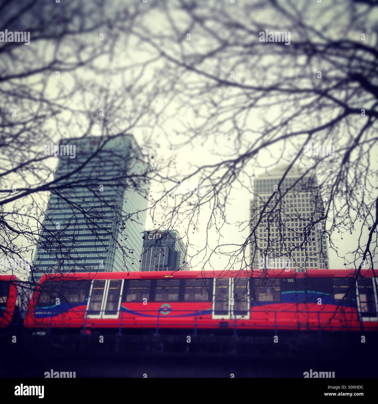 DLR train passing the skyscrapers in Canary Wharf, London. - Stock Image