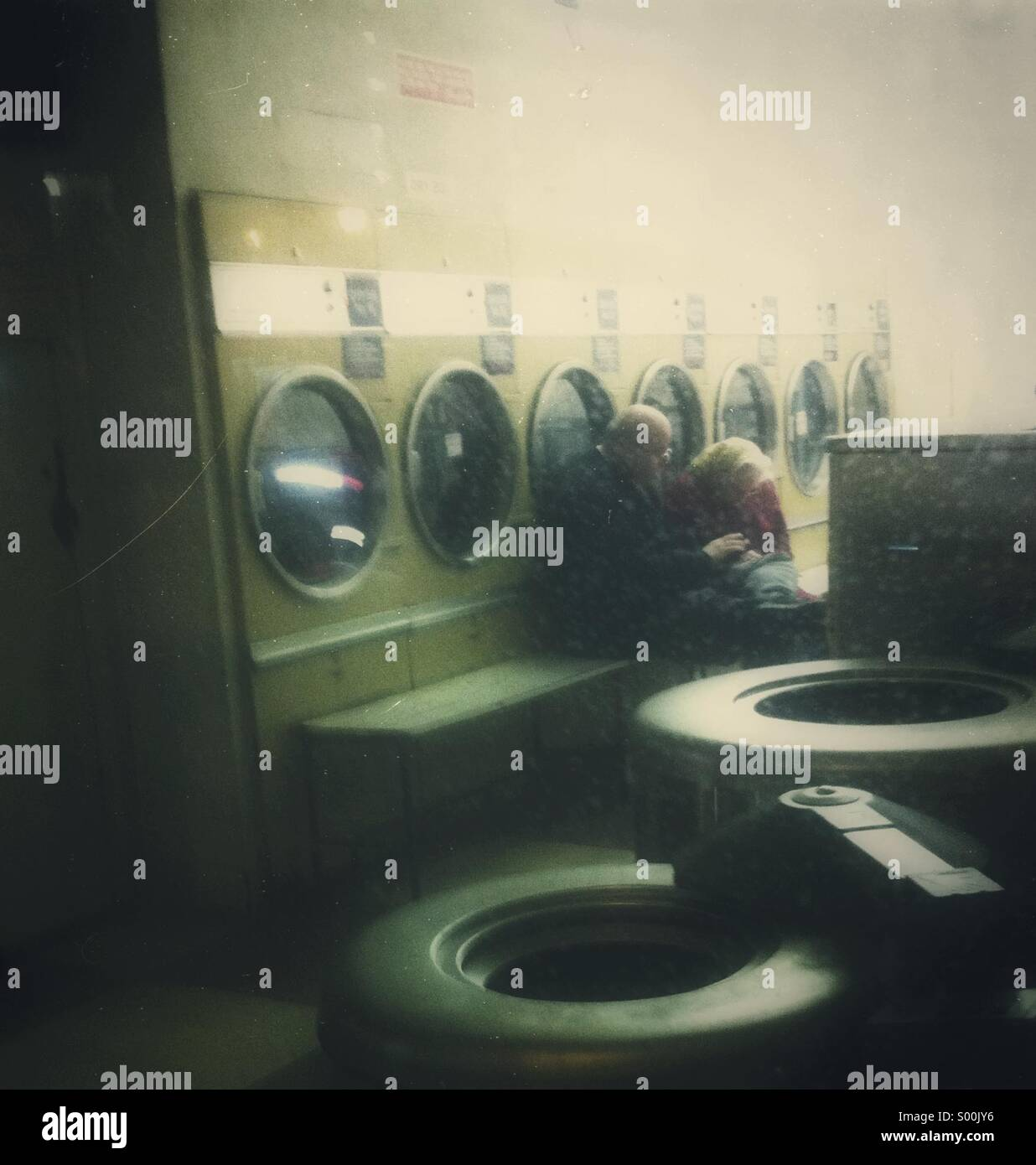 Couple sitting together in laundrette at night - Stock Image