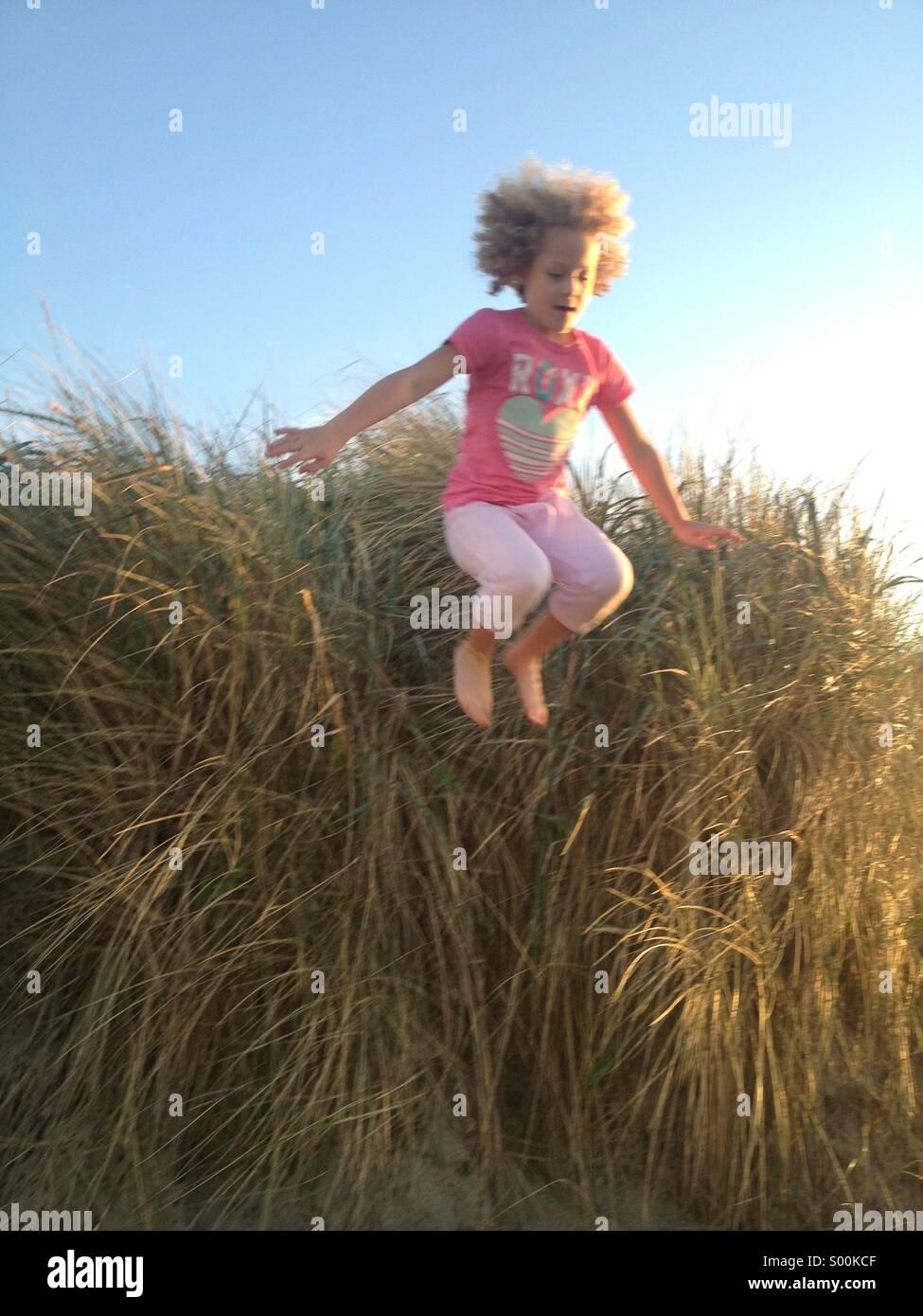 Jumping off sand dune, 7-year old Maya Braibish jumps off sand dune on July 4th. Manzanita, Oregon Coast - Stock Image