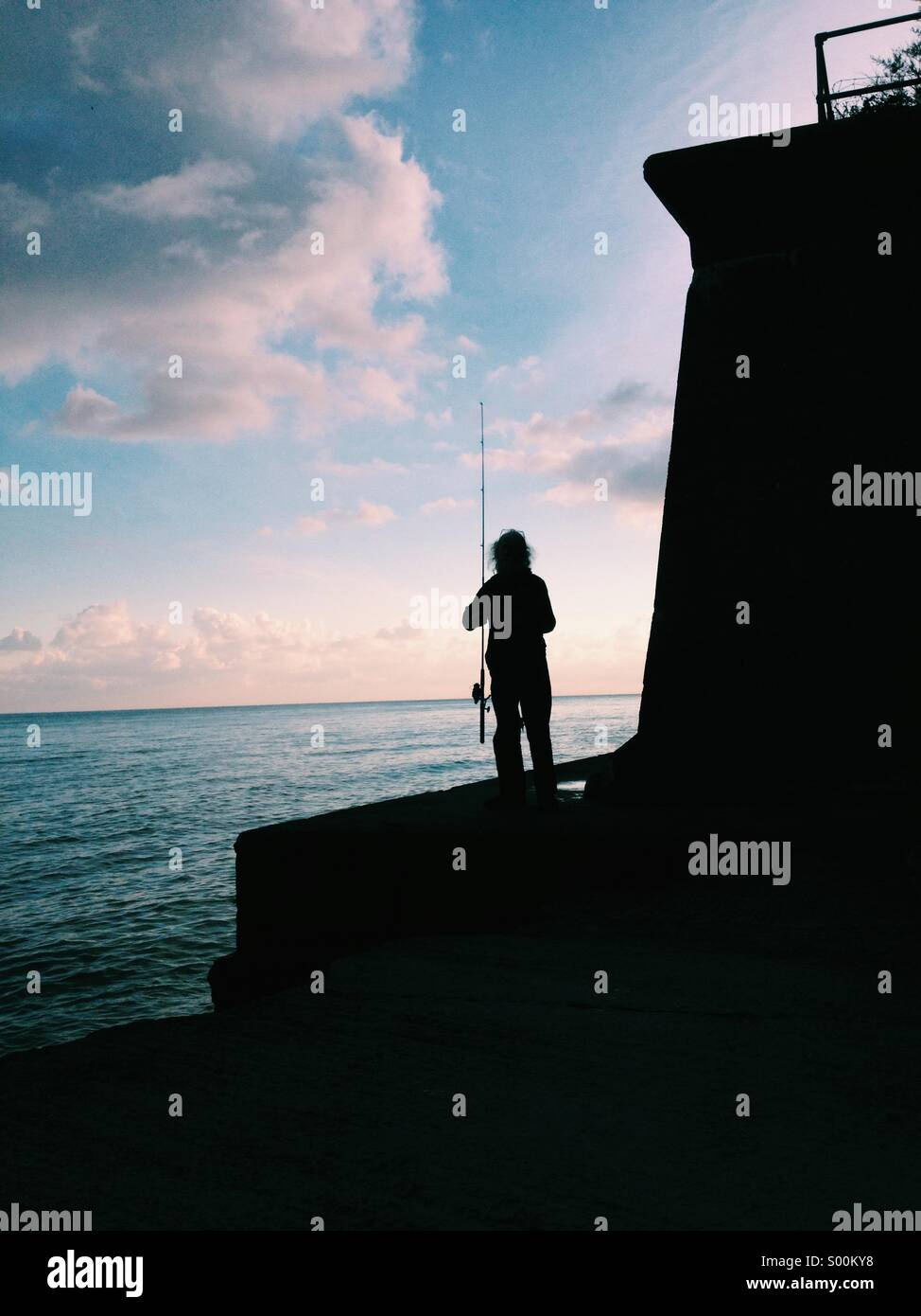 Sillouette of a fisherman by the sea - Stock Image