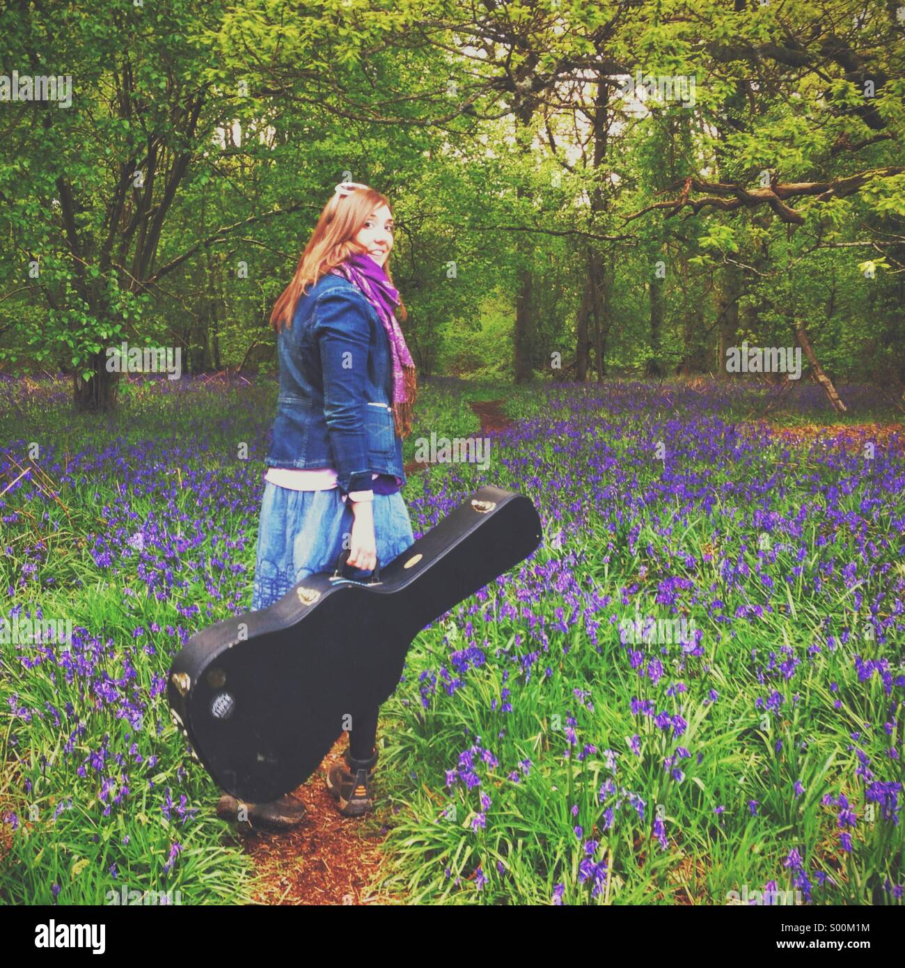 Woman walking with guitar among bluebells - Stock Image
