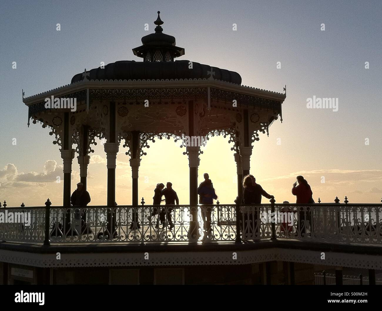 Silhouetted shapes of people dancing on Brighton's seafront bandstand at sunset, East Sussex, England - Stock Image