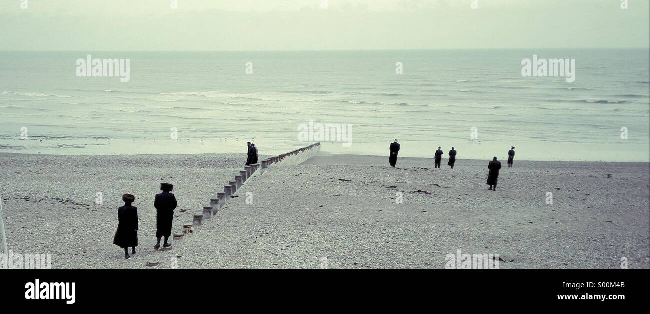 Orthodox Jews enjoying a stroll on a wintry Eastbourne beach, East Sussex, England. - Stock Image