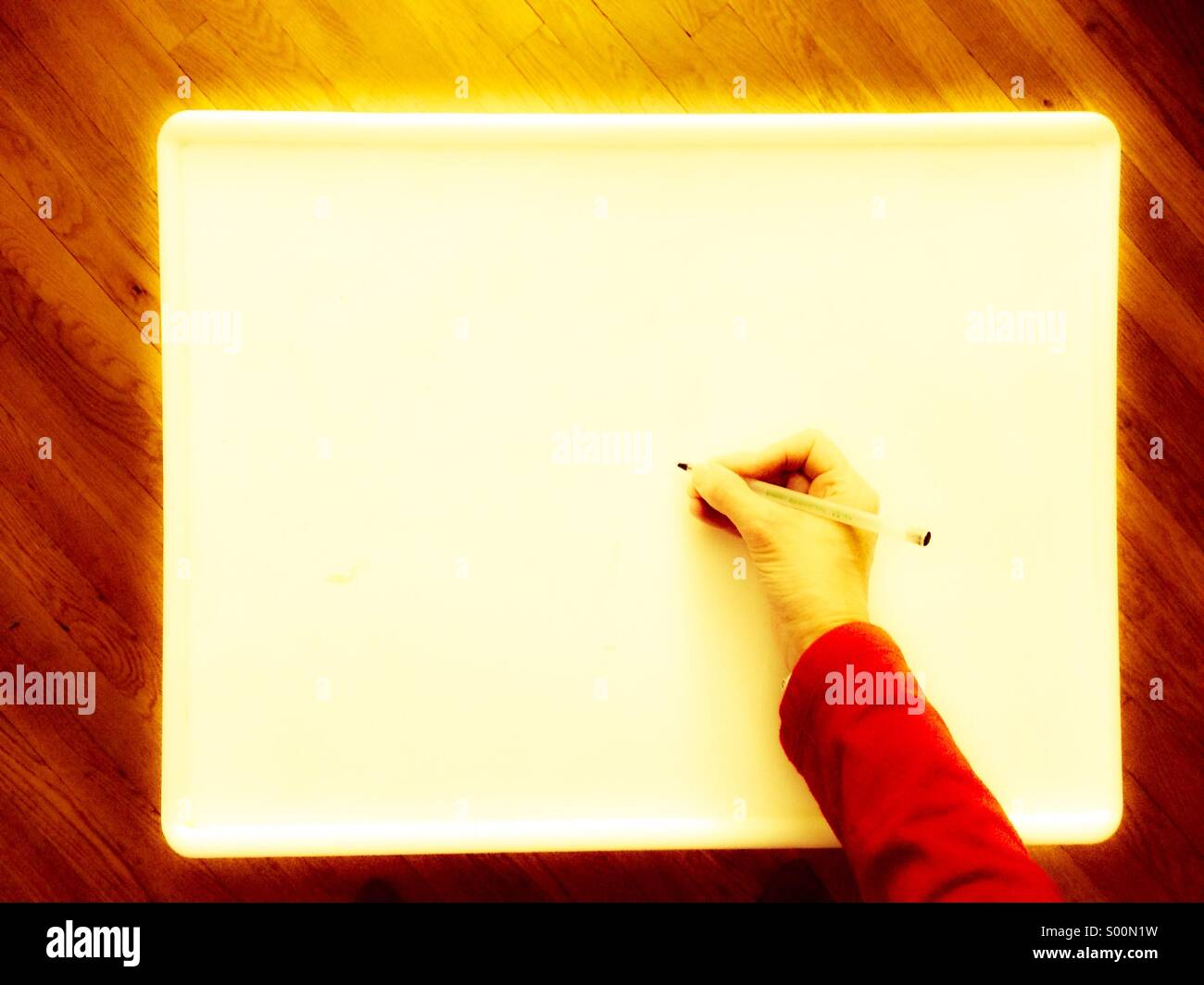Hand holding pen to write on blank white sign, seen from above - Stock Image