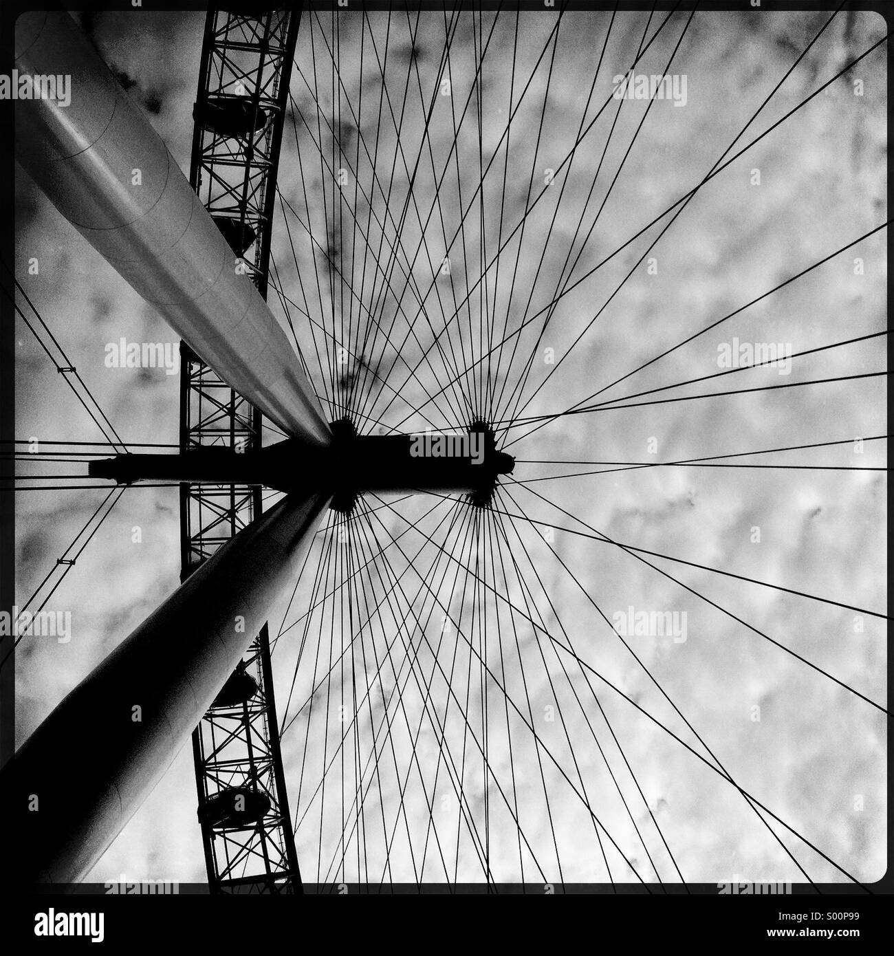 Abstract black and white photo of the London Eye against a mottled cloudy sky - Stock Image