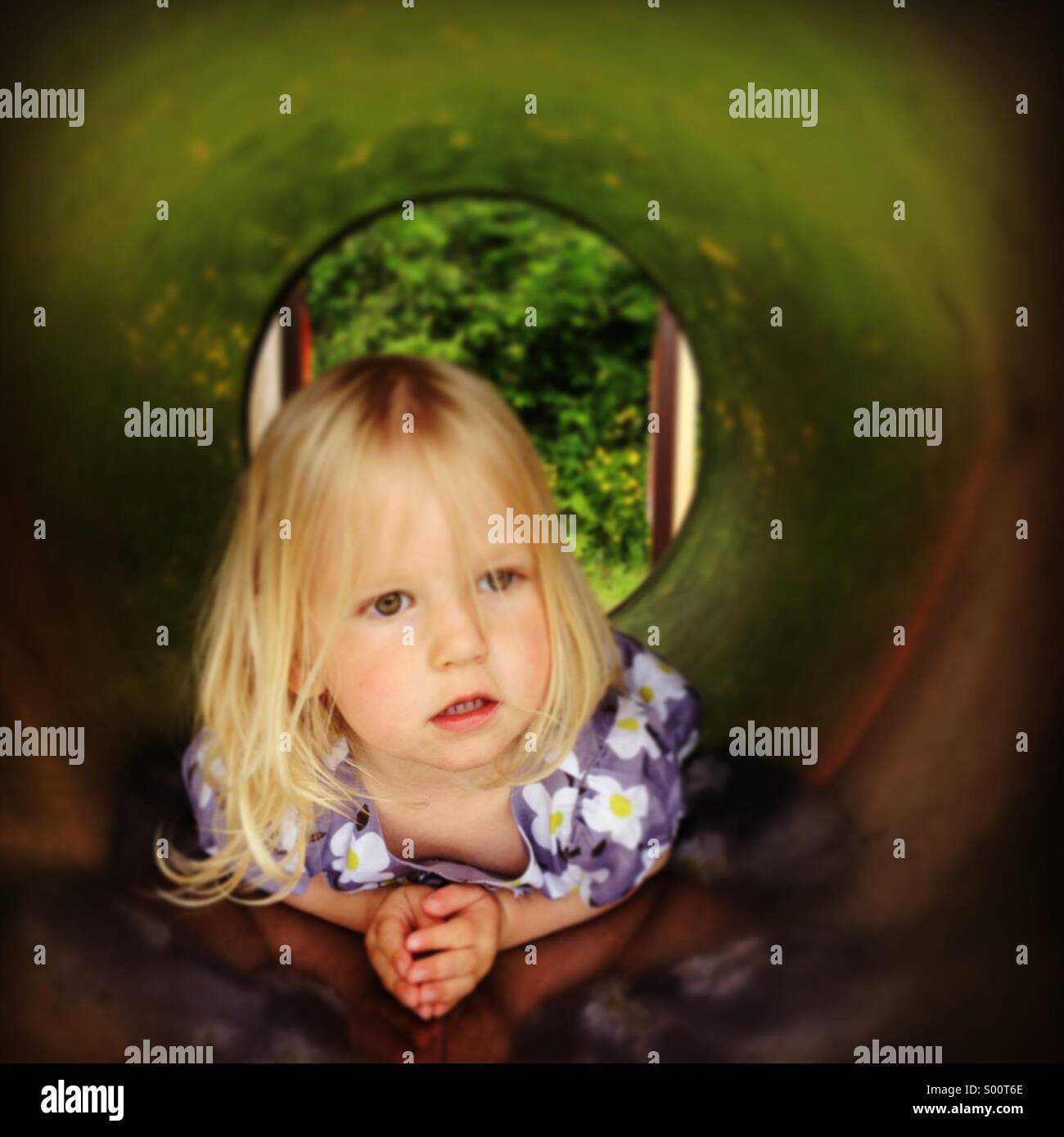 A young girl hiding in a tunnel in a playground - Stock Image