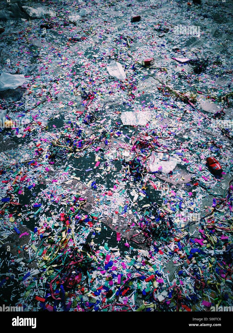 Confetti and streamers covering the street after a carnival - Stock Image