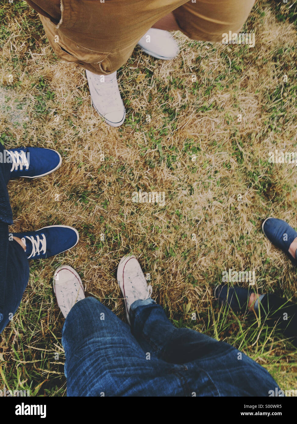 Four pairs of trainers on Grass - Stock Image