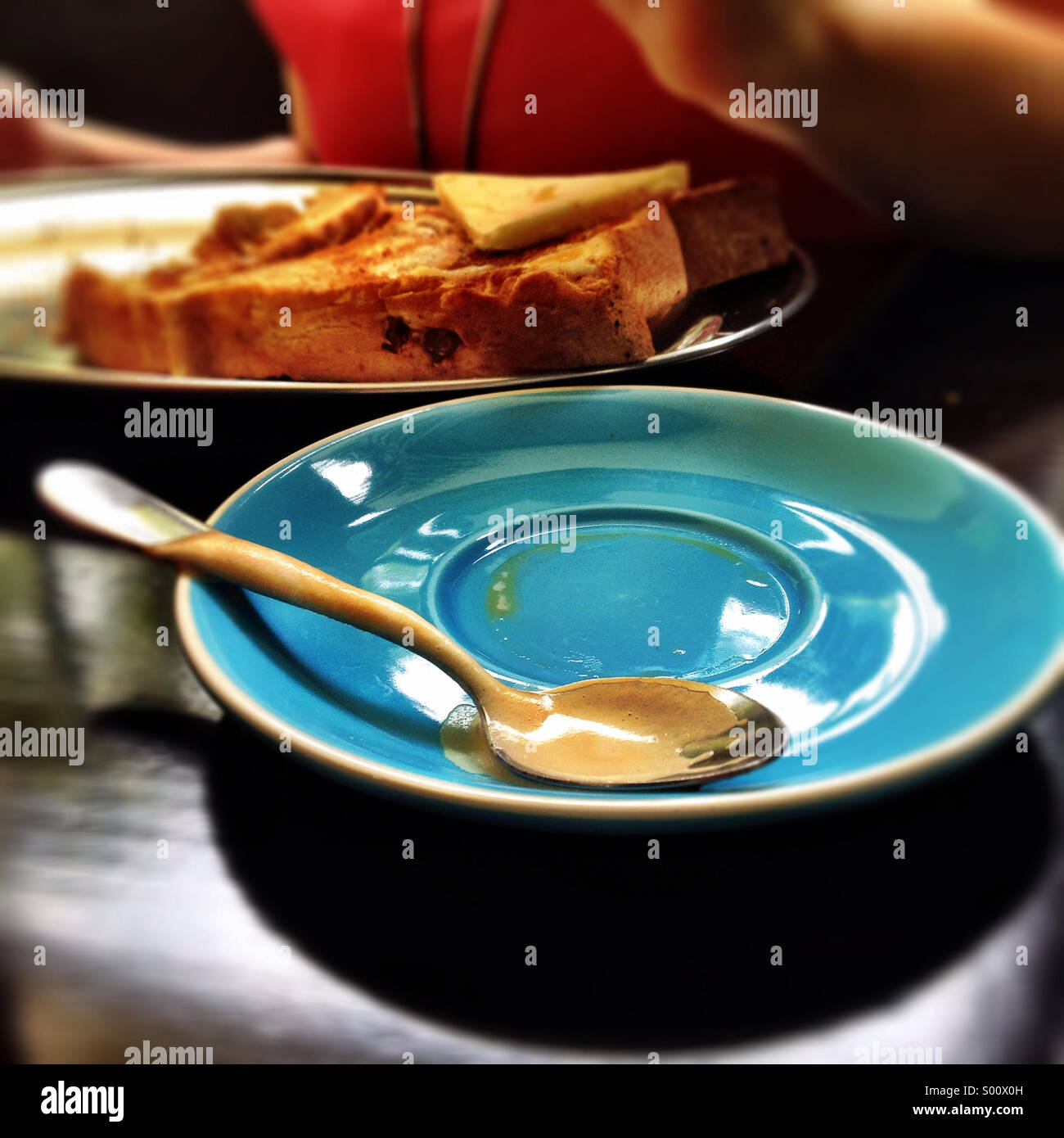 Coffee spoon on a saucer - Stock Image