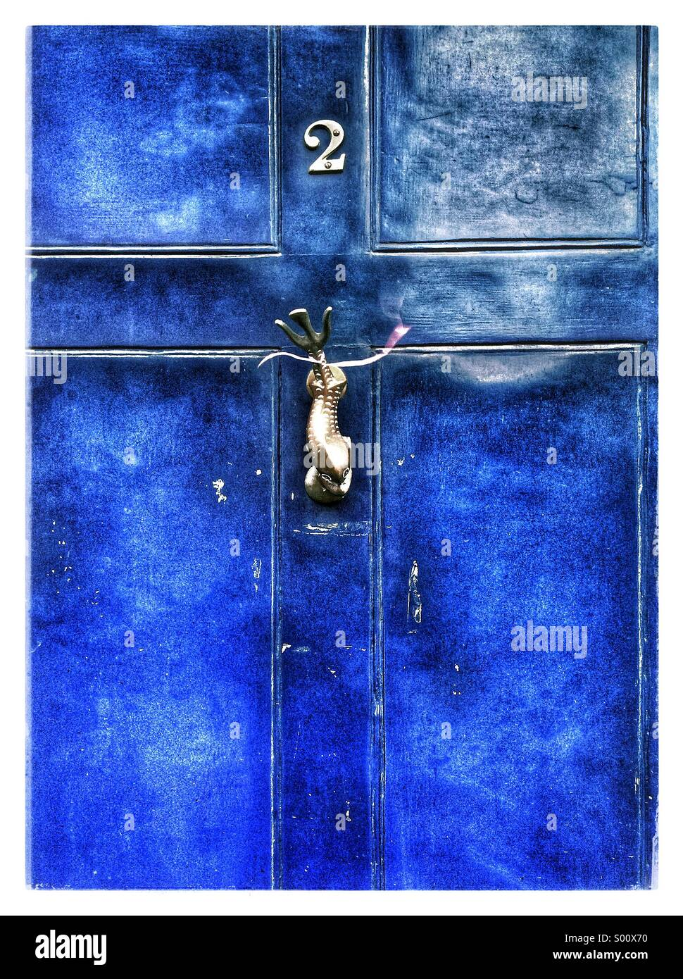 A bright blue colored door with a fish shaped knocker. - Stock Image