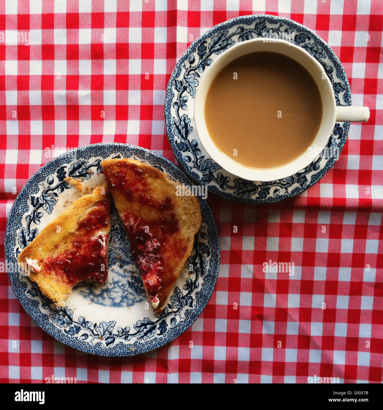 Tea and toast in vintage blue and white crockery, on a red and white gingham tablecloth - Stock Image