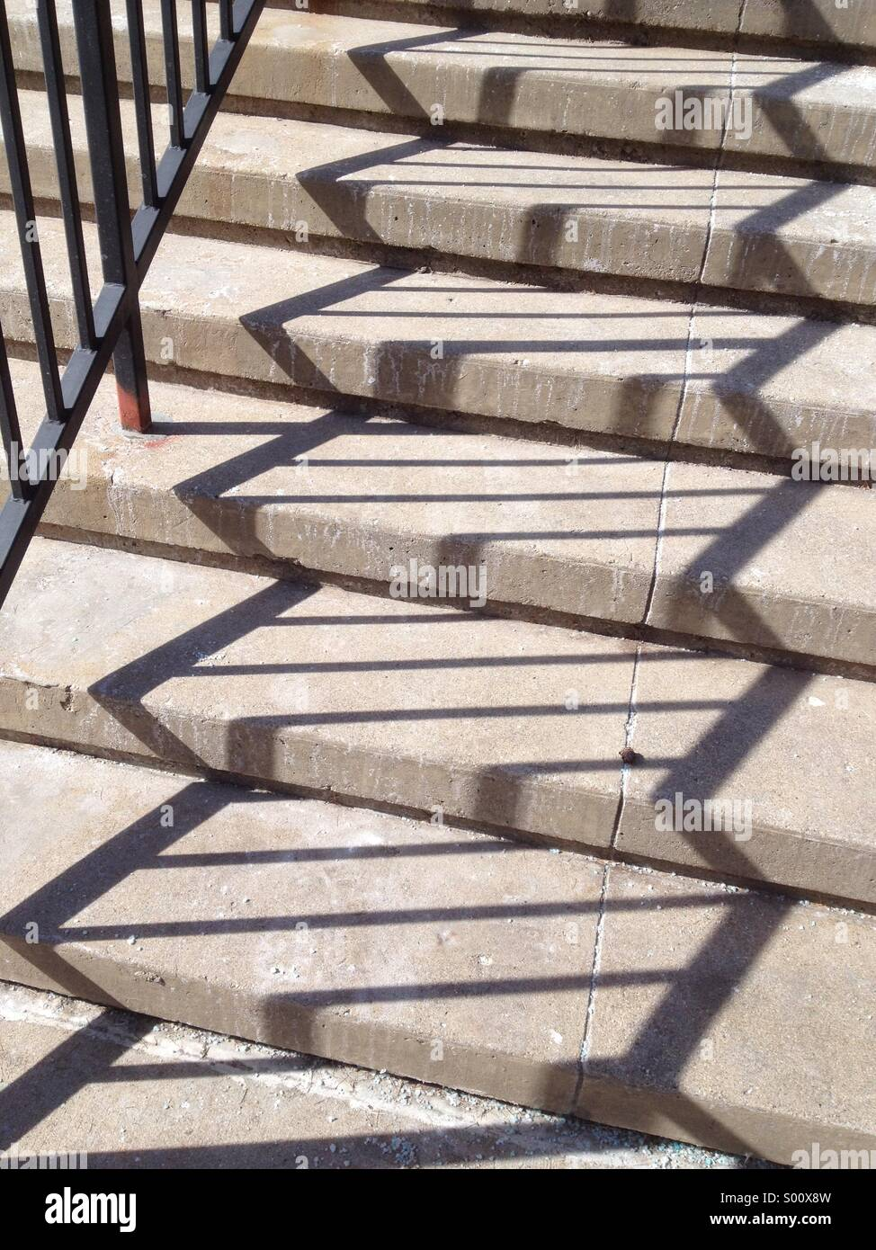 Zigzag pattern of shadows of iron railing along concrete steps on a sunny day - Stock Image