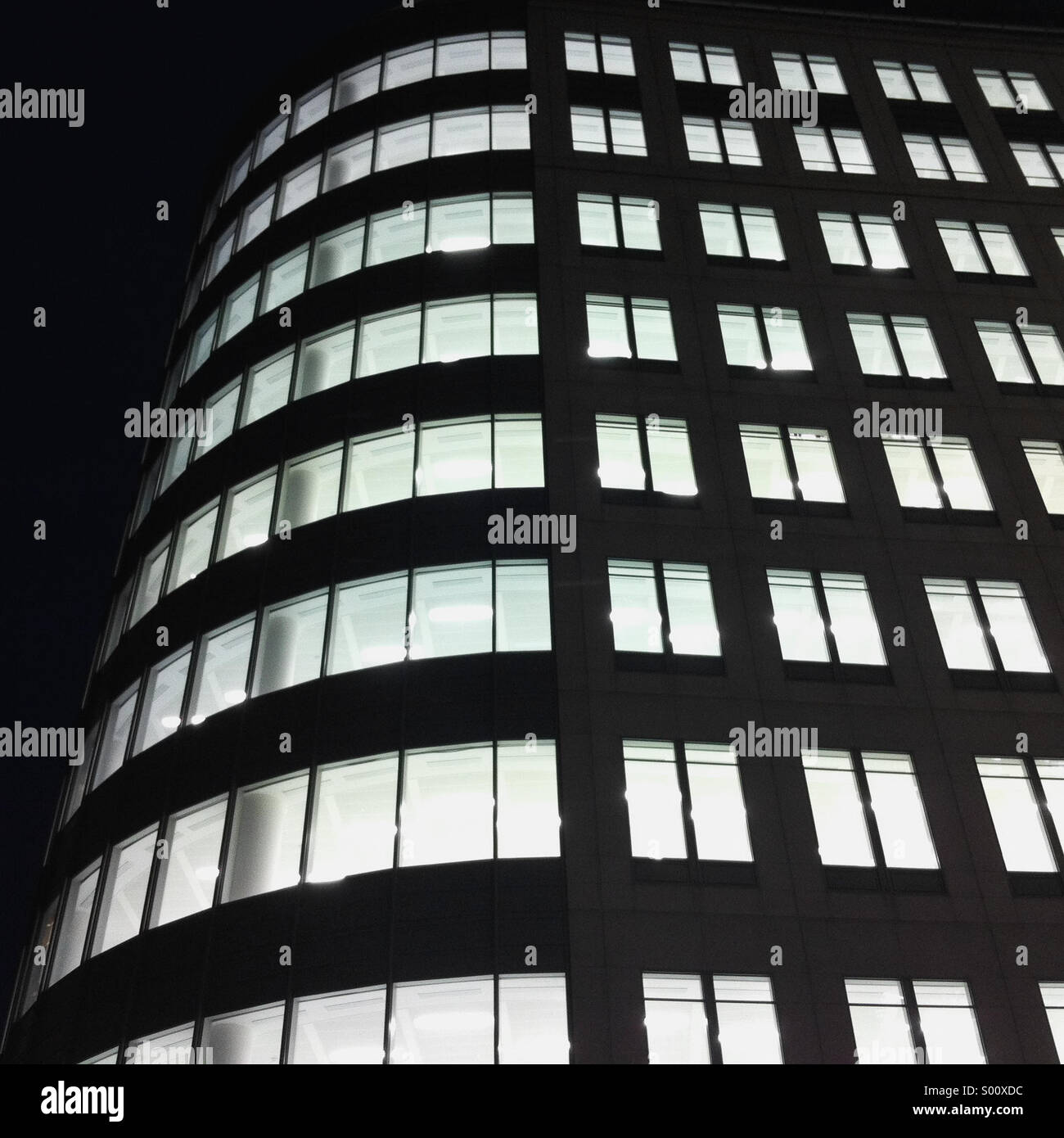 Lights on in an empty building in the city or London - Stock Image