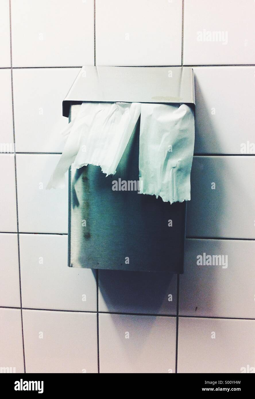 Toilet tissue hangs from a waste receptacle on a white tile wall in a public washroom. - Stock Image