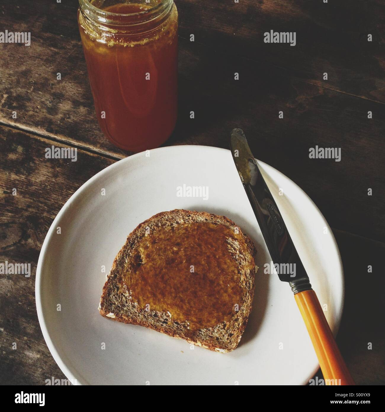 Organic raw honey on bread. - Stock Image