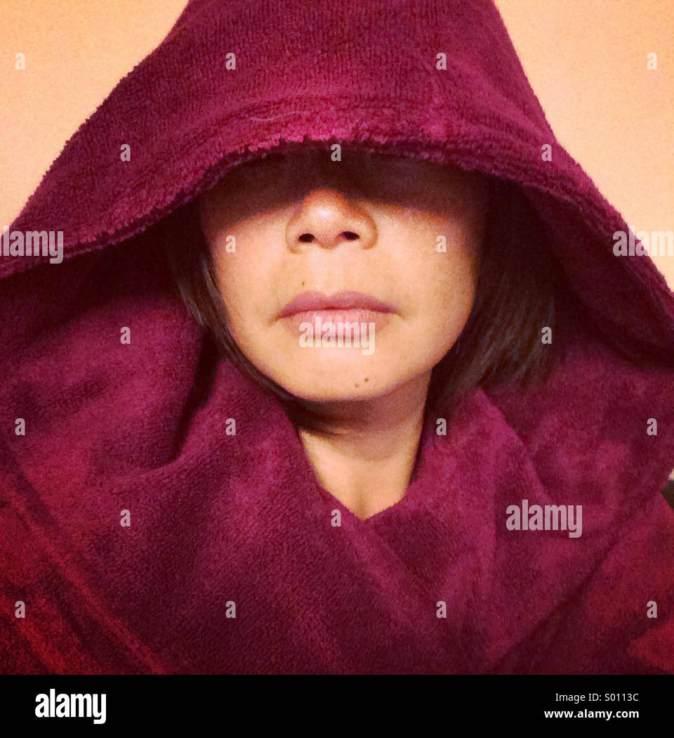 Face of Woman in fuschia garment with hood draw over eyes - Stock Image