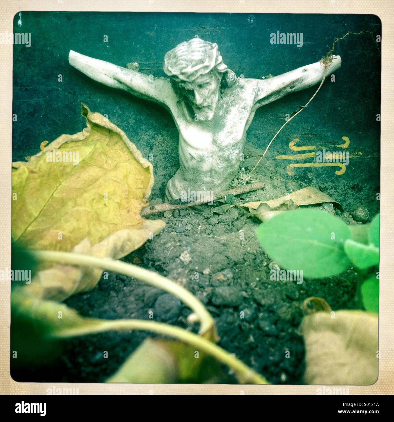 A sculpture of Jesus Christ crucified missing his hands decorates a tomb full of tree leaves during Day of the Dead - Stock Image