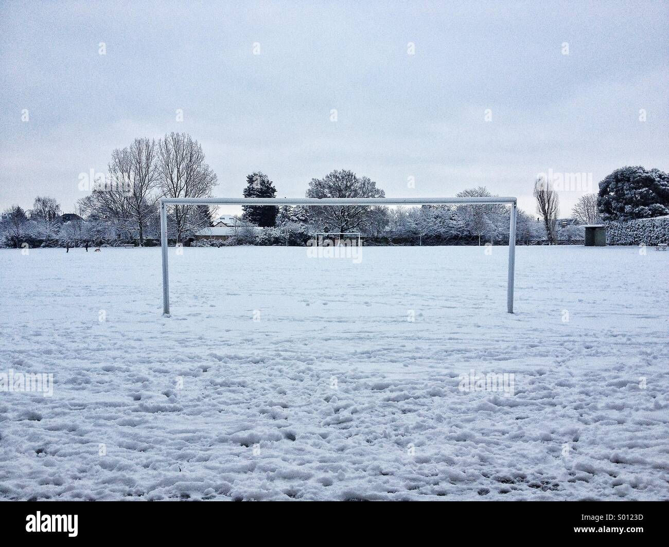 Frozen football pitch in snow, London, UK - Stock Image