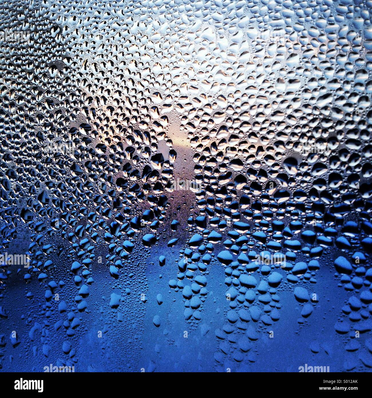 Condensation on a window during a winter sunrise - Stock Image