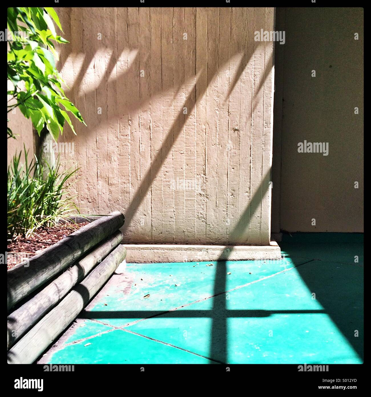 Shadows cast on a wall and floor in an outdoor setting in the middle of the day. - Stock Image