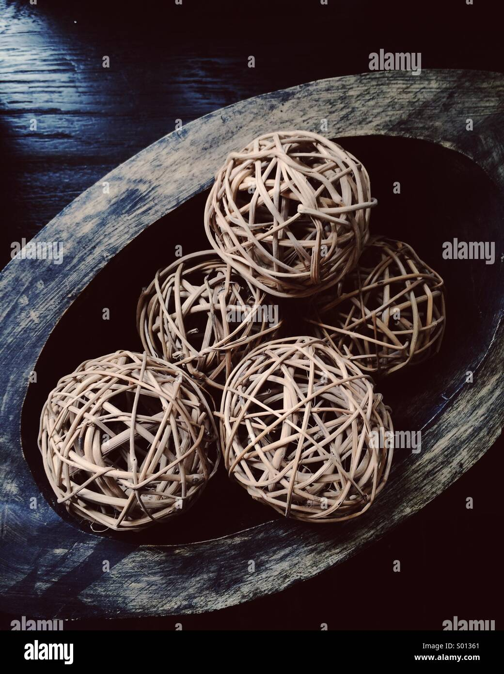 Rustic woven balls in wooden dish - Stock Image