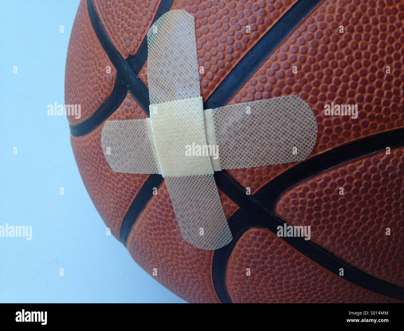 Temporary fix: Two bandages crisscrossed on basketball - Stock Image
