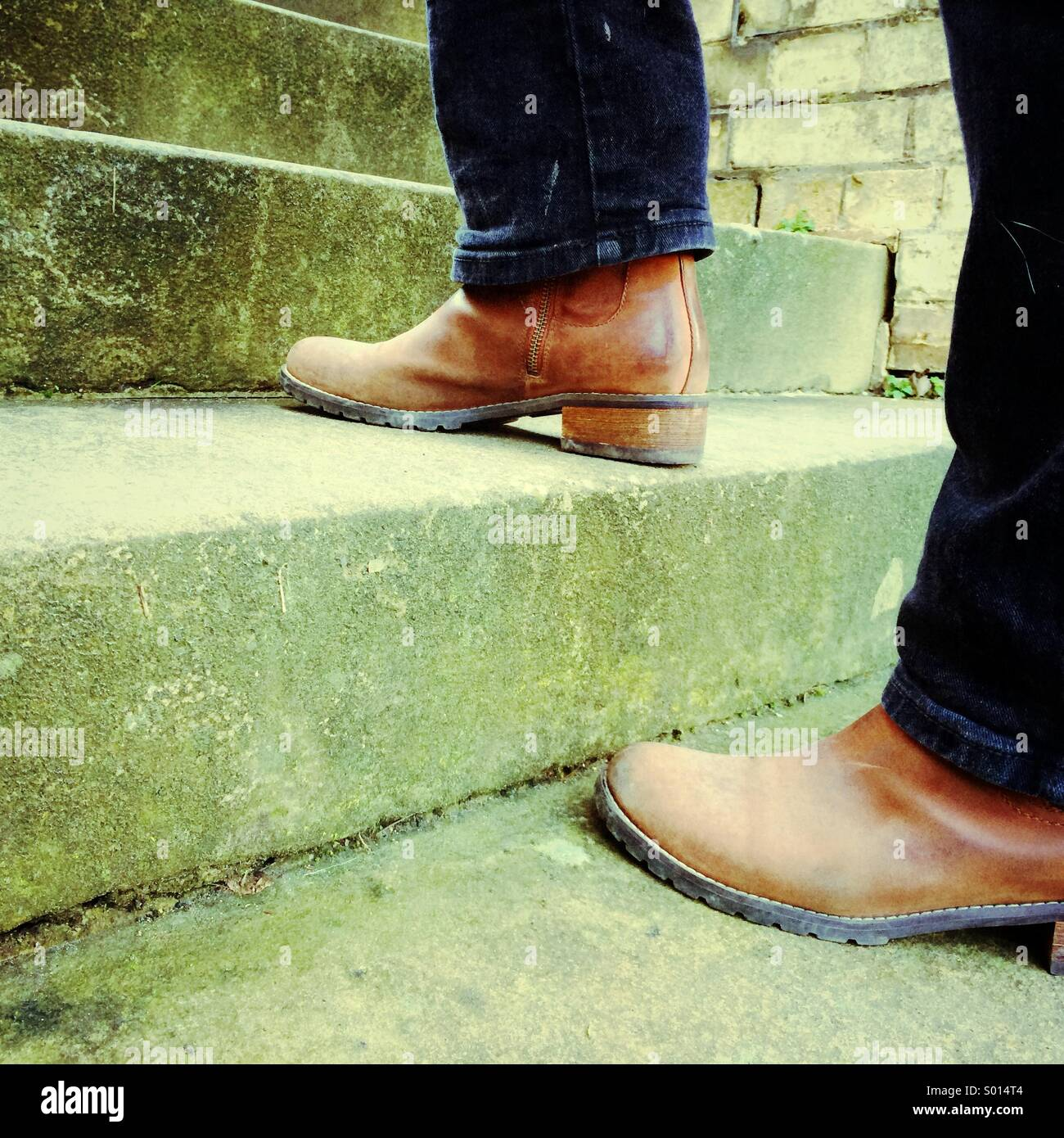 Woman's legs in black jeans and brown boots shown climbing stone steps - Stock Image